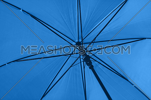 Close up blue colorful vivid umbrella personal perspective low angle view