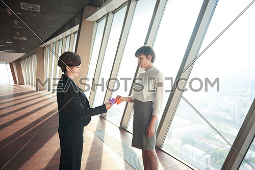 business woman group assembling jigsaw puzzle and represent team support and help concept, top view perspective at modern bright office interior