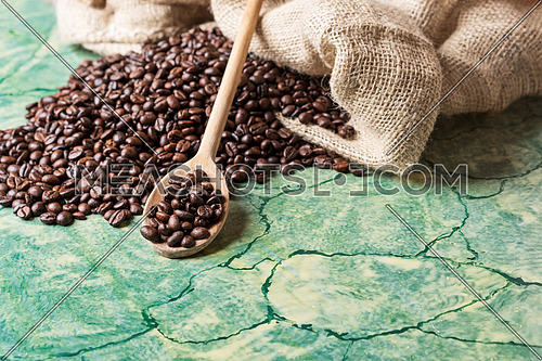 Coffee beans in coffee burlap bag on green table and wooden spoon with coffee beans on top.