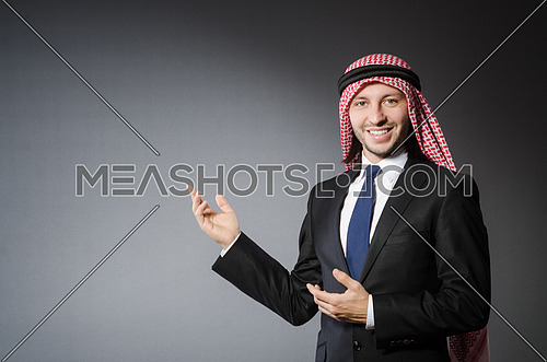 Arab businessman pointing to something or somebody against grey background