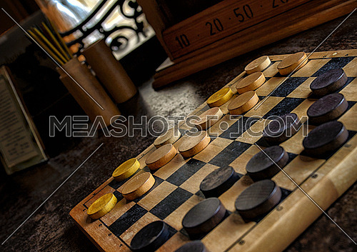 A checker board placed on a wooden table