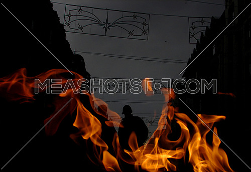 fire in the foreground while two men are in the shadows