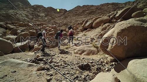Follow shot for group of tourists climbing big rocks with bedouin guide to explore Sinai Mountain for wadi Freij at day.