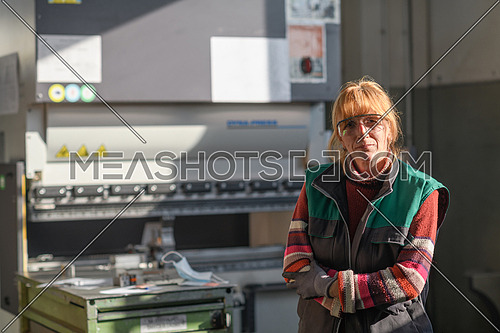 portrait of a woman standing in front of a CNC machine in goggles and working in a modern metal production and processing factory. High quality photo