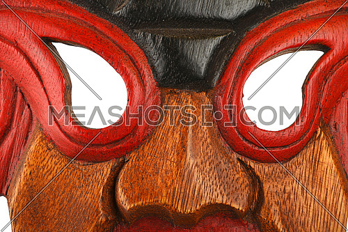Asian traditional wooden mask with face of human or demon painted with vivid red and blue close up