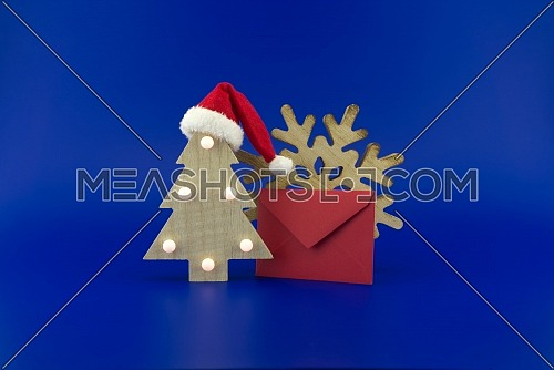 Christmas tree with a Santa hat on top next to a red envelope for greetings and a snowflake decoration on a festive blue background. New Year and Christmas greeting season concept