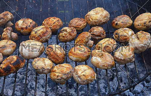 White champignons portobello mushrooms being cooked on char grill