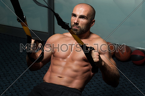 Attractive Man Does Push Ups With Trx Fitness Straps In The Gym's Studio