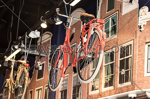 A red bicycle is hanging in a store