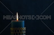 Blue candle with straw twigged holder trembling flame close up out of the dark blue background, off-center, blown out