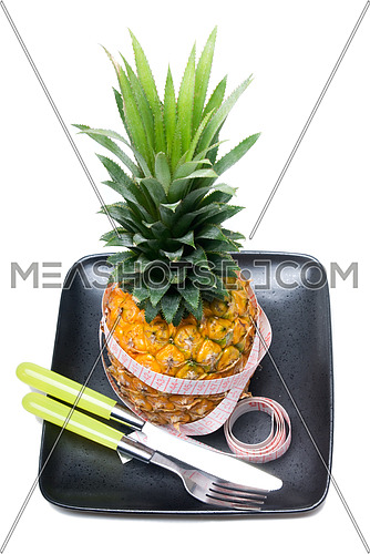 pineapple on a black plate with tape meter,knife and fork isolated on white background