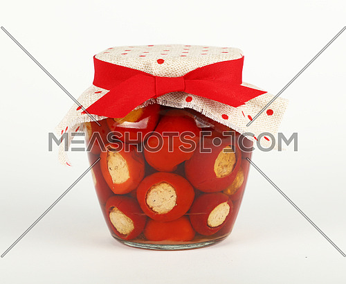 Close up of one glass jar of pickled red hot cherry chili pepperoncini peppers stuffed with soft ricotta cheese, with linen canvas lid decoration and red ribbon over white background, low angle side view