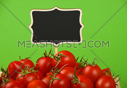 Red ripe fresh small cherry tomatoes with black wooden chalkboard price sign tag close up over green background