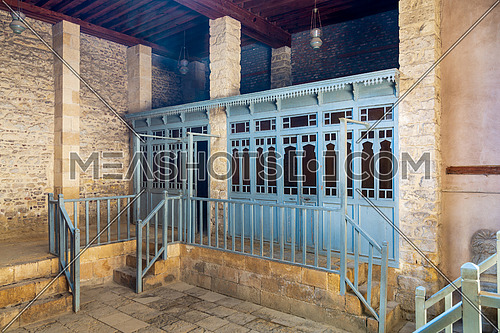 Changing rooms with blue wooden door shutters and wooden balustrades at abandoned historical traditional Turkish public bathhouse, Moez Street, Cairo, Egypt