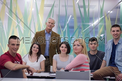 portrait of confident teacher,  students group in background