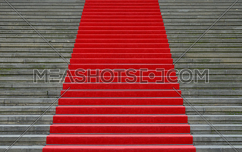 Close up red carpet over grey concrete stairs perspective ascending, low angle view