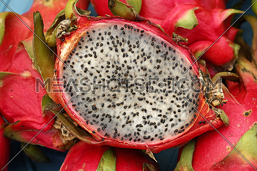 Close up several red ripe pitaya or white pitahaya dragon fruit with one cut cross section half on market stall, high angle view