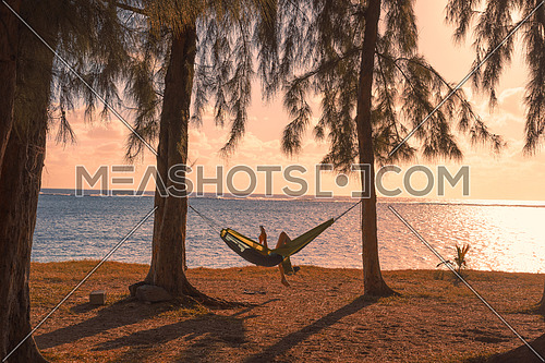 Silhouette of woman reading tablet in hammock,used split toning effect.