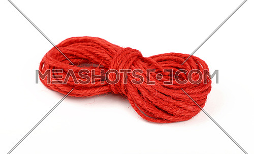 Small coil skein of natural red jute twine rope isolated on white background, close up, high angle view