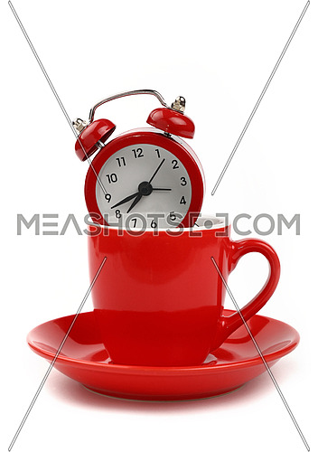 Coffee time concept, small red metal alarm clock with red bells in coffee cup or teacup with saucer, over white background, close up, low angle side view