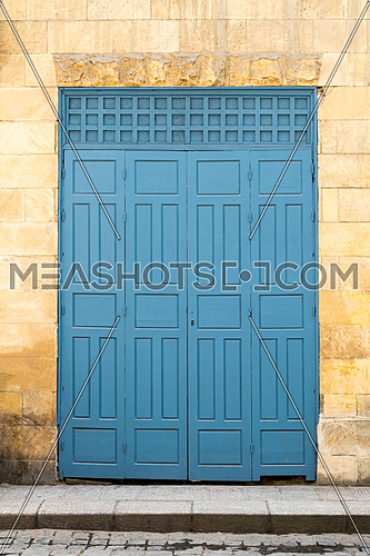Vintage antique folding wooden decorated blue door over yellow stone wall