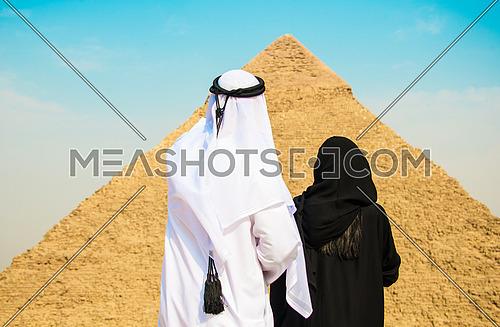 an Emiratie man and his wife looking at the giza pyramids