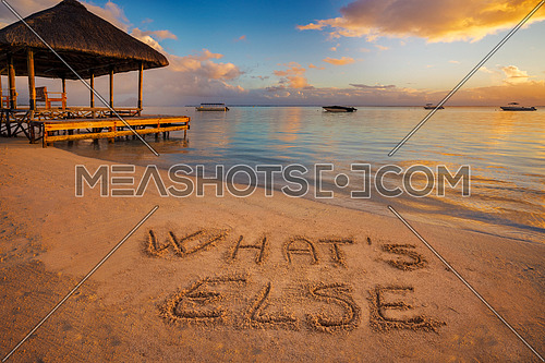 "Forground written in the sand ""What's else"" at sunset in Mauritius Island with Jetty silhouette and Fishermen's boats in the background."