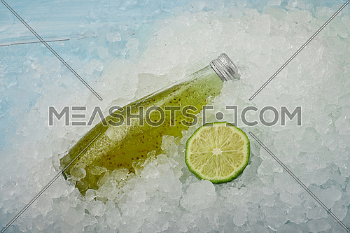 Close up one glass bottle of cold green juice cocktail drink with chia seeds and half cut lime on crushed ice at retail display, high angle view