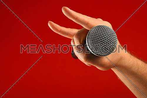Man hand holding voice microphone with devil horns rock metal gesture sign over red background, side view