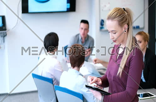 Pretty blond usinesswoman Using Tablet In Office Building during conference