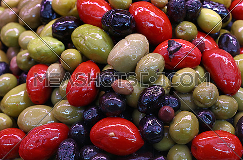 Mix of assorted whole Italian olives (black, green, red) in oil close up, retail market stall display, high angle view