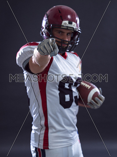 Portrait of American football player pointing against gray background