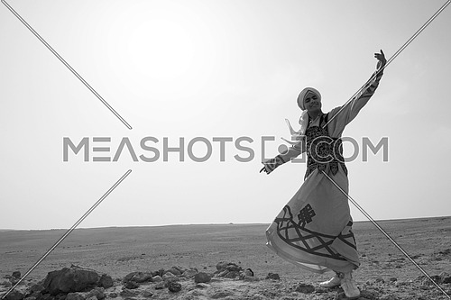 a black and white image of a traditional Egyptian sufi dancer performing in the desert