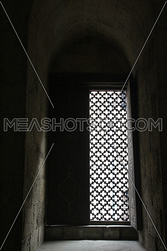 a photo from inside a historical mosque in Islamic Cairo, Egypt showing  architecture  style used at that time  and a window