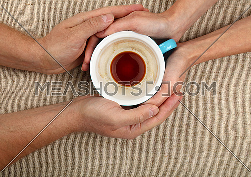 Man and woman hands holding and hugging together big empty cup of black coffee over canvas tablecloth, close up, elevated top view