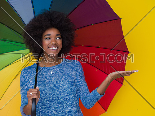 Portrait of young beautiful african american woman holding a colorful umbrella isolated on a Yellow background