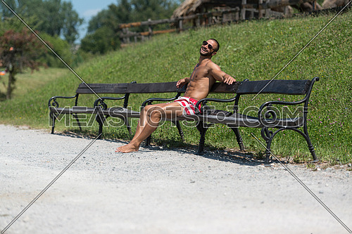 Smiling Athlete With Naked Torso Sitting And Resting On Bench