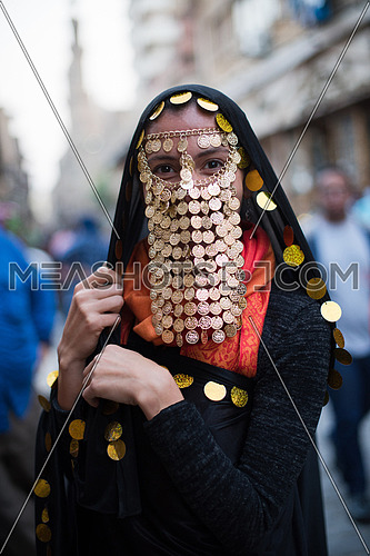 portrait of a young middle eastern woman in a traditional costume with gold coins over her face