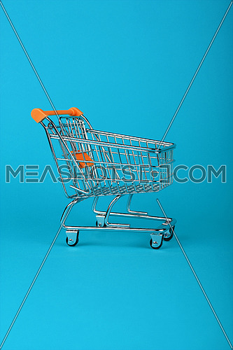 Close up empty toy metal supermarket shopping cart over pastel blue background with copy space, low angle side view