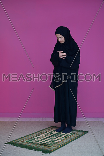 Muslim woman in namaz praying to Allah, God. Muslim woman on the carpet praying in traditional middle eastern clothes, Woman in Hijab