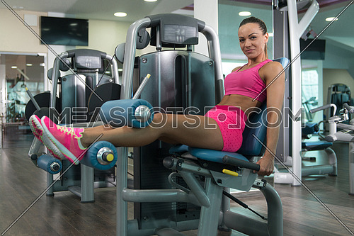 Young Woman Working Out Legs On Machine In A Gym - Leg Exercise