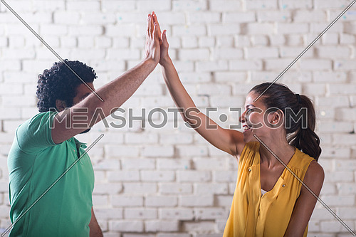 two young middle eastern informal businessman celebrating success with high five to each other in creative office