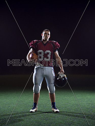 portrait of young confident American football player on field at night