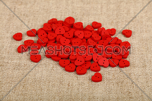 Red heart shaped handmade wooden sewing buttons on linen canvas, high angle view, close up