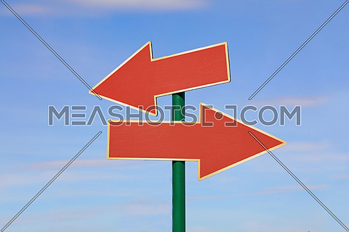 Road signpost with two red brown blank copy space arrows directing to different directions, left and right, over clear blue sky, low angle side view