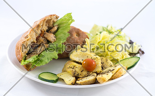 A plate with a sandwich, salad and potatoes