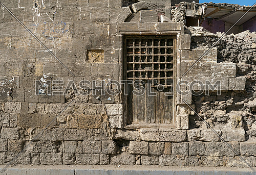 Old abandoned wall with closed wooden window covered by broken wooden ornate grid, El-Dard El-Ahmar, Cairo, Egypt