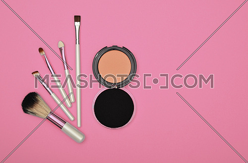 Close up set of face makeup blush, beige sponge and brush over pink background, elevated top view, directly above
