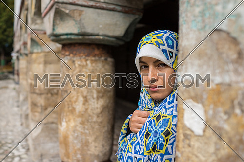 A veiled Muslim woman outdoors standing alone