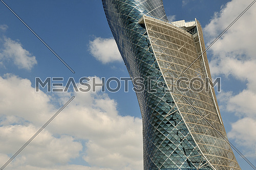 modern building of steel and glass facade with blue sky and clouds in background